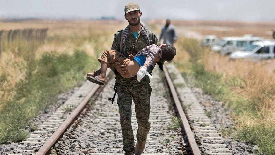 A Kurdish People's Protection Units (YPG) fighter carries a boy injured by what they said was a mine after they fled Maskana town in the Aleppo countryside and make their way towards the Turkish border in Tel Abyad. (File photo: Reuters)