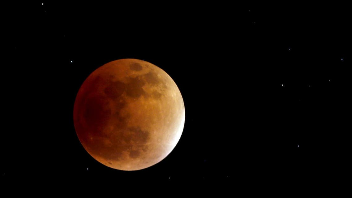 The moon, appearing in a dim red colour, is covered by the Earth's shadow during a total lunar eclipse in Bogota