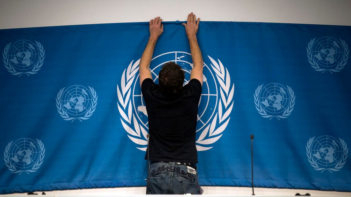 A worker sets up a United Nations banner at the media center in preparations for the start of this week's Syria peace talks in Montreux and Geneva, in Montreux, Switzerland, Tuesday, Jan. 21, 2014. Russia and Iran on Tuesday criticized the U.N. chief's decision to withdraw Tehran's invitation to join the peace conference on Syria, as diplomats said a new report on Syrian regime atrocities underscored the urgent need to try to end the country's brutal civil war. (AP Photo/Anja Niedringhaus)