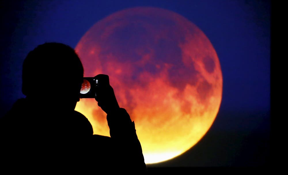 A man takes picture of the screen displaying the moon in Warsaw. (Reuters)