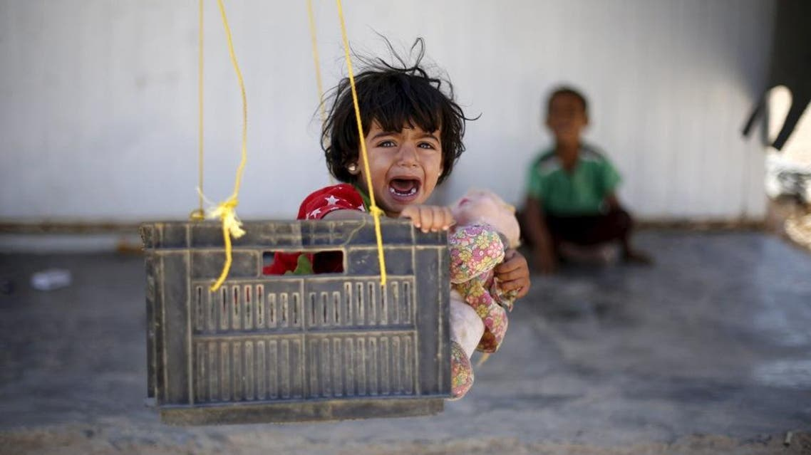A Syrian refugee child reacts while sitting in a swing in Al Zaatari refugee camp, in the Jordanian city of Mafraq. (Reuters)