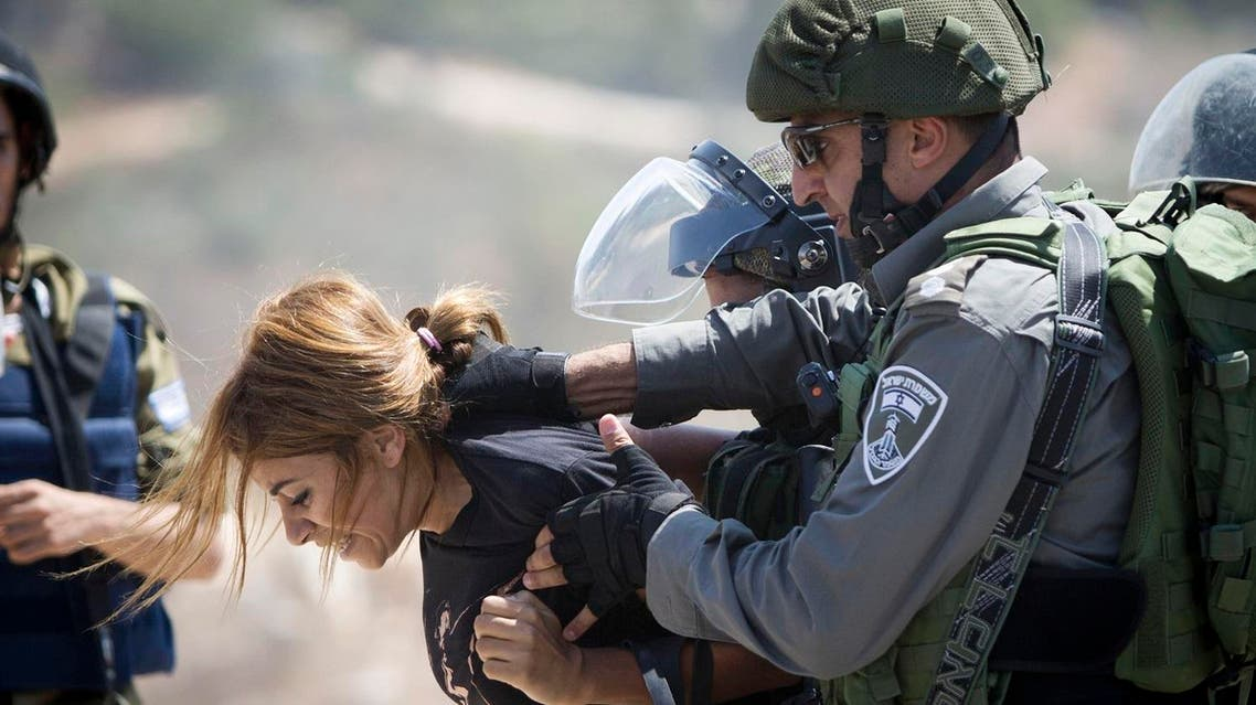 An Israeli border police officer detains a Palestinian woman during a protest against the expansion of the nearby Jewish settlement of Halamish, in the West Bank village of Nabi Saleh near Ramallah. (File photo: AP)