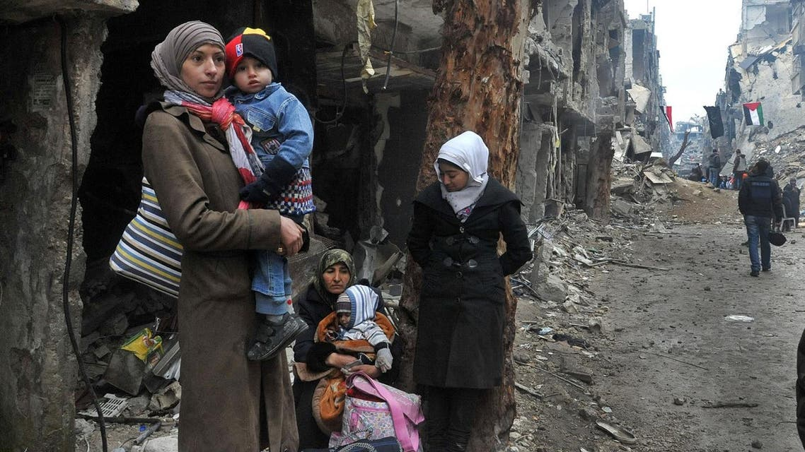 In this Feb. 4, 2014, file photo released by the Syrian official news agency SANA, residents of the besieged Yarmouk Palestinian refugee camp wait to leave the camp on the southern edge of the Syrian capital Damascus. (AP)