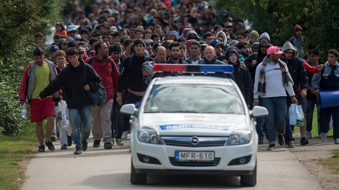Migrants walk behind a police car in the Hungarian border town of Hegyeshalom toward the border of Austria on Monday Sept. 28, 2015.