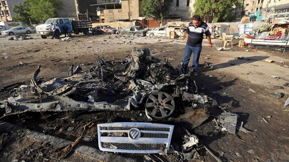 A civilian inspects the aftermath of a car bombing near a restaurant in a commercial area of central Baghdad, Iraq, Tuesday, Sept. 29, 2015. Iraqi officials say a car bomb exploded around midnight Monday in central Baghdad killing and wounding civilians. (AP Photo/Hadi Mizban)
