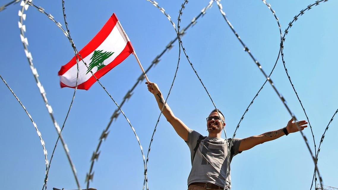 A Lebanese anti-government protester is seen through barbed wire as he waves his national flag, on a road leading to the parliament building where Lebanese political leaders held their third dialogue session. (File photo: AP)