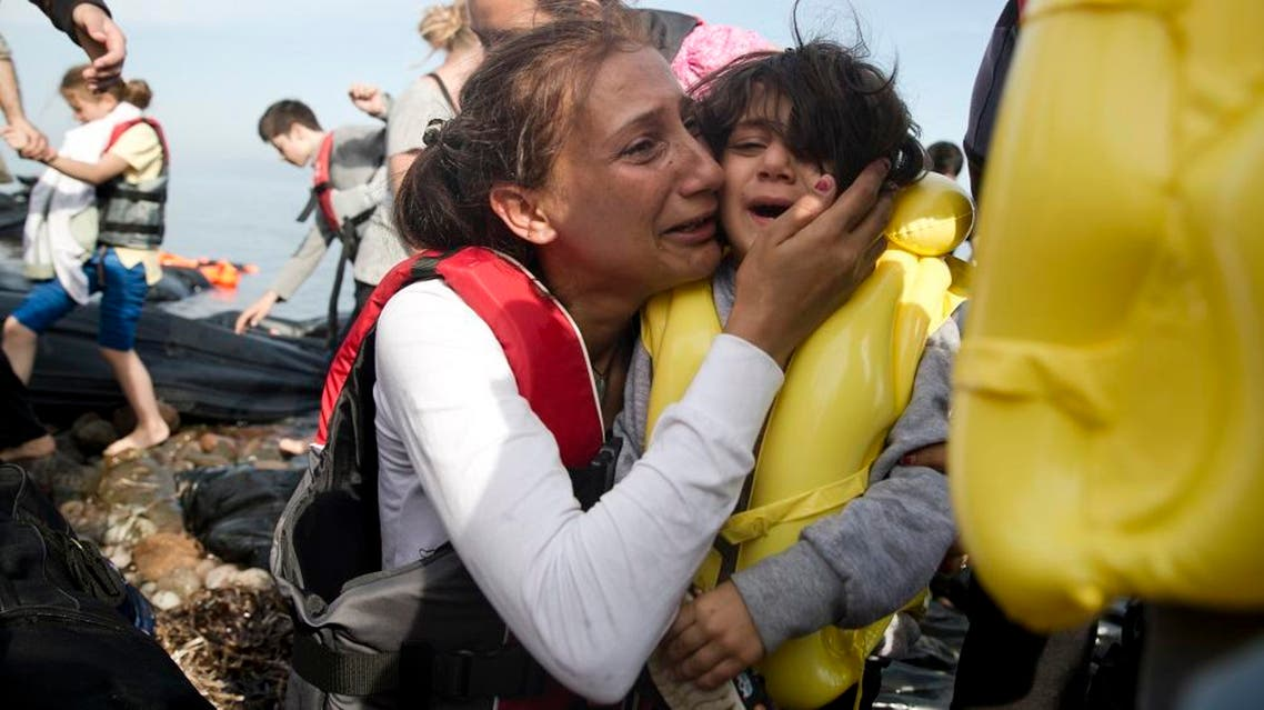 A Syrian woman and her child react after they arrived with others from Turkey on the shores of the Greek island of Lesbos, on a inflatable dinghy, Sunday Sept. 27, 2015. More than 260,000 asylum-seekers have arrived in Greece so far this year, most reaching the country's eastern islands on flimsy rafts or boats from the nearby Turkish coast.(AP Photo/Petros Giannakouris)