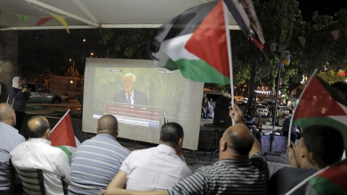Palestinians wave Palestinian flags as they watch on a large screen the speech of Palestinian President Mahmoud Abbas in the 70th session of the United Nations General Assembly, near Damascus Gate, outside Jerusalem's Old City. (Reuters)