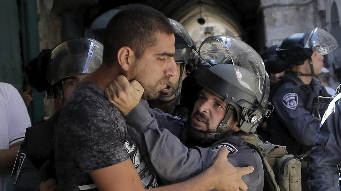 An Israeli policeman prevents a Palestinian man from entering in Occupied Jerusalem's Old City. (Reuters)