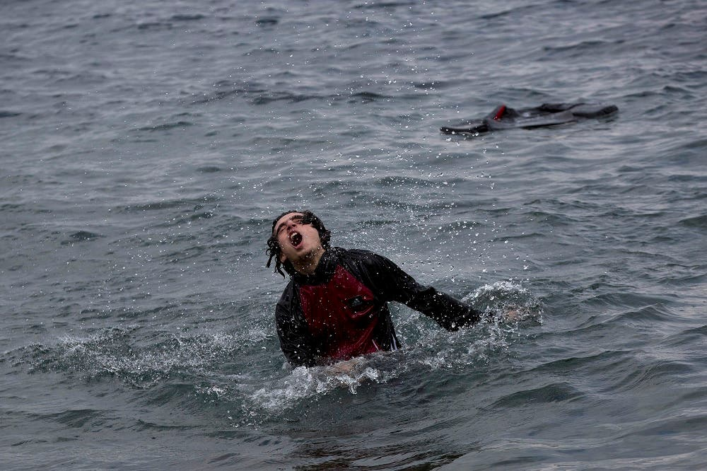 A Syrian refugee splashes in the water as he approaches the shores of Lesbos island after jumping from a inflatable dinghy that carried him with others from Turkey to Greece on Wednesday, Sept. 23, 2015. More than 260,000 asylum-seekers have arrived in Greece up to this point, most reaching the country's eastern islands on flimsy rafts or boats from the nearby Turkish coast. (AP Photo/Petros Giannakouris)