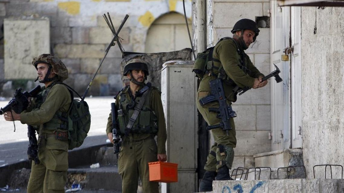 An Israeli army soldier breaks a building's lock to get to the roof during clashes with Palestinians over tension in Jerusalem's al-Aqsa mosque, in the occupied West Bank city of Hebron September 29, 2015. REUTERS