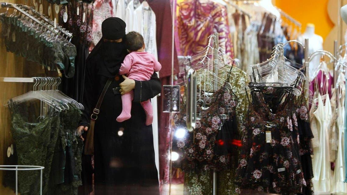 A Saudi woman holding a child checks out lingerie at a store in Riyadh, Saudi Arabia. (File photo: AP)