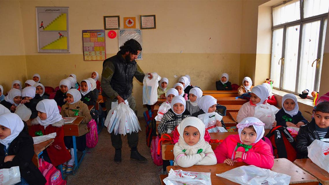 """FILE - In this photo released on Jan. 11, 2015, by a militant website, which has been verified and is consistent with other AP reporting, an Islamic State militant, center, distributes plastic bags full of stationery and other gifts to Iraqi young students at a school classroom in Mosul, northern Iraq. When world leaders convene for the U.N. General Assembly debate Monday, Sept. 28, 2015, it will be a year since the U.S. president declared the formation of an international coalition to """"degrade and ultimately destroy"""" the Islamic State group. Despite billions of dollars spent and thousands of airstrikes, the campaign appears to have made little impact. (Militant website via AP, File)"""