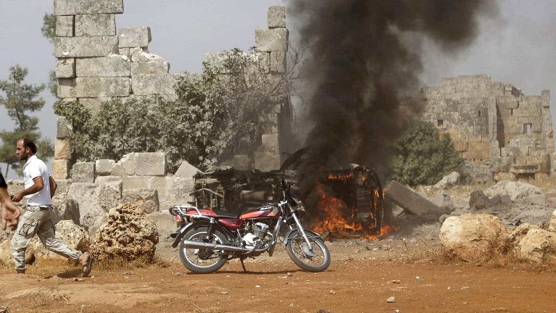 A man runs past a burning military vehicle at a base controlled by rebel fighters from the Ahrar al-Sham Movement in the southern countryside of Idlib. (Reuters)