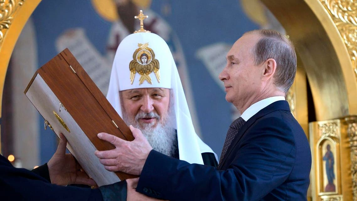 Russian President Vladimir Putin, right, looks at an icon while listening to Russian Orthodox Church Patriarch Kirill. (AP)