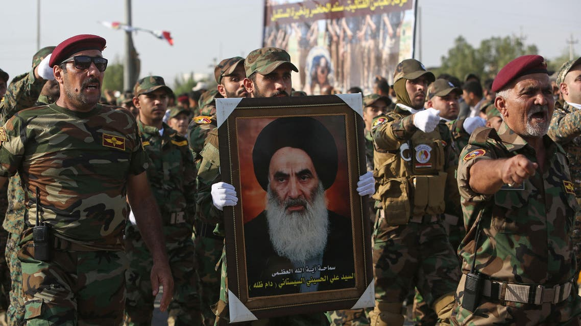 Members of the Abbas combat squad, a Shiite militia group, carry a picture of spiritual leader Grand Ayatollah Ali al-Sistani during a parade in Basra, 340 miles (550 kilometers) southeast of Baghdad, Iraq, Saturday, Sept. 26, 2015. Iraqi security forces and allied Shiite militias are training together to try to regain Iraqi cities under Islamic State control, officials said. (AP Photo/Nabil al-Jurani)