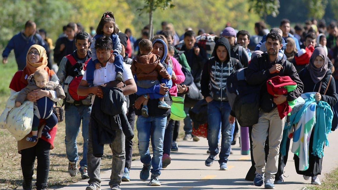 Migrants walk to the border between Hungary and Austria in Hegyeshalom, Hungary, Thursday, Oct. 1, 2015. The European Union is threatening to take action against Hungary over laws it has introduced to limit the flow of migrants through its territory. (AP Photo/Ronald Zak)