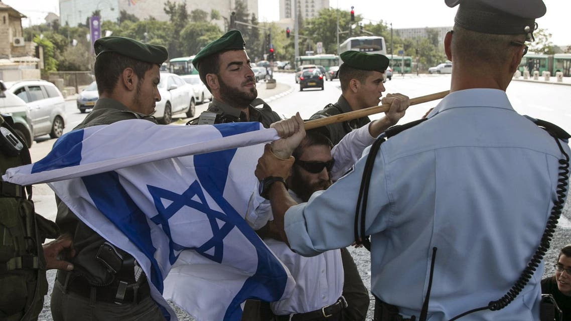 A right-wing Israeli protester is removed by border policemen as he tries to block a street in Jerusalem during a demonstration against the killing of an Israeli couple October 2, 2015. (Reuters)