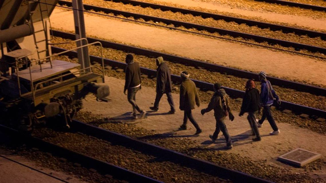Migrants walk along the train tracks after crossing a fence as they attempt to access the Channel Tunnel in Calais, Friday, Aug. 7, 2015.