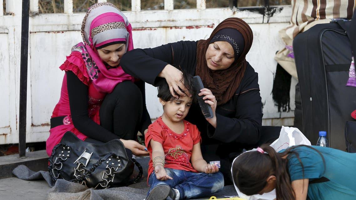 لاجئون سوريون ينتظرون في مرفئ طرابلس بلبنان لركوب عبارة إلى تركيا