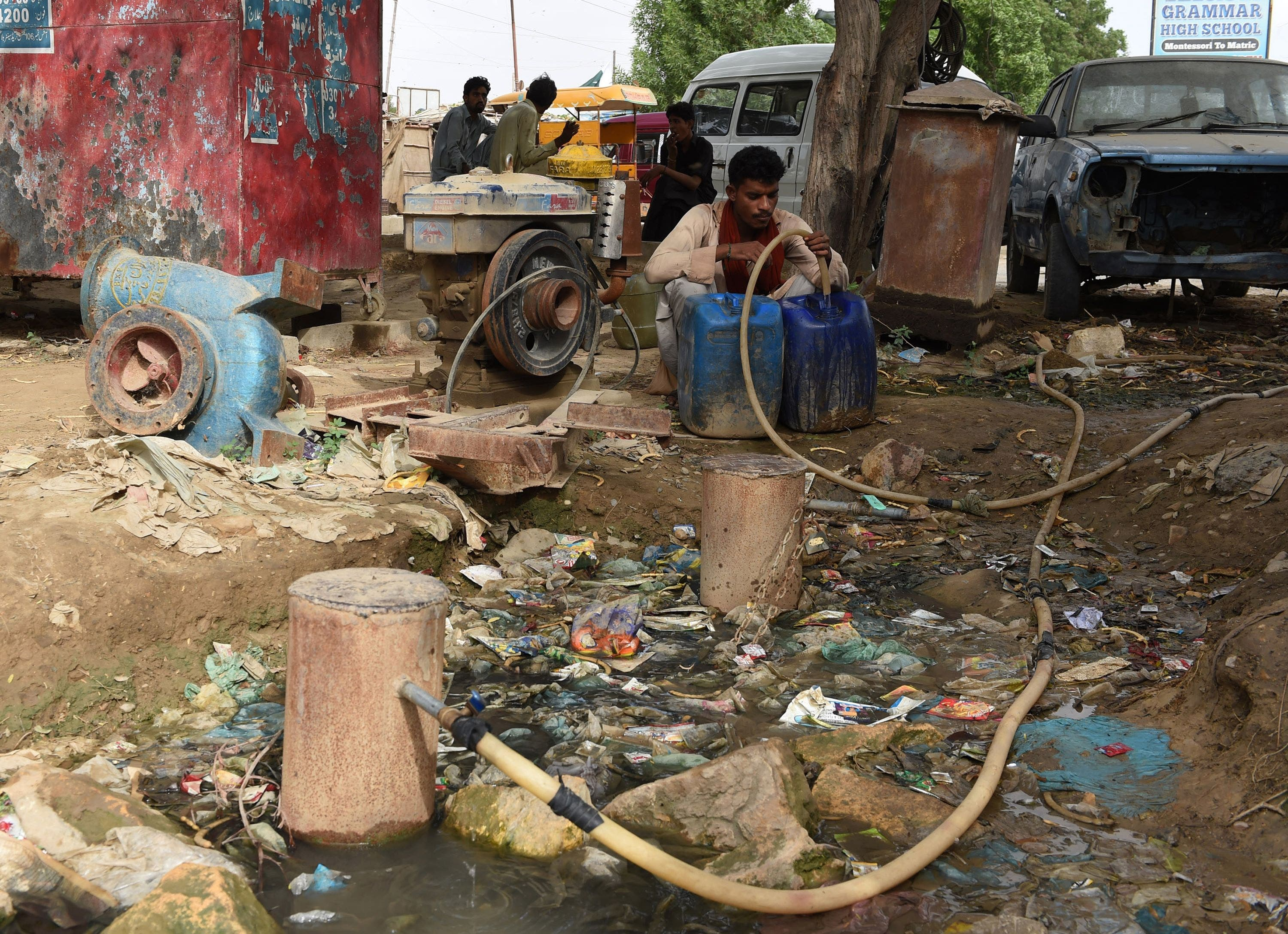 In this photograph taken on August 20, 2015, a Pakistani man fills a container with water in a slum area of Karachi.