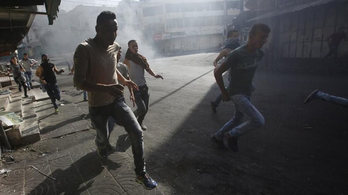 Palestinians run for cover during during clashes with Israeli troops in the occupied West Bank city of Hebron October 4, 2015. (Reuters)
