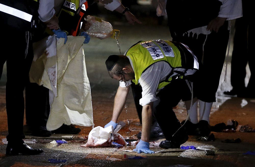 A member of the Zaka Rescue and Recovery team cleans blood stains at the scene where a Palestinian was shot dead after he stabbed and killed two people in Jerusalem's Old City October 3, 2015.