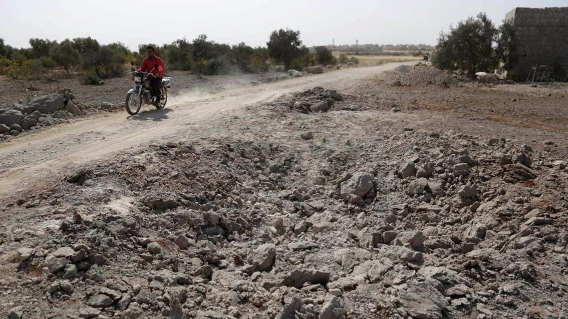 A man rides a motrobike past a site hit overnight by what activists aid were airstrikes carried out by Russian air force near a camp for displaced people on the outskirts of al-Ghadfa town in the southern countryside of Idlib, Syria. (File: Reuters)