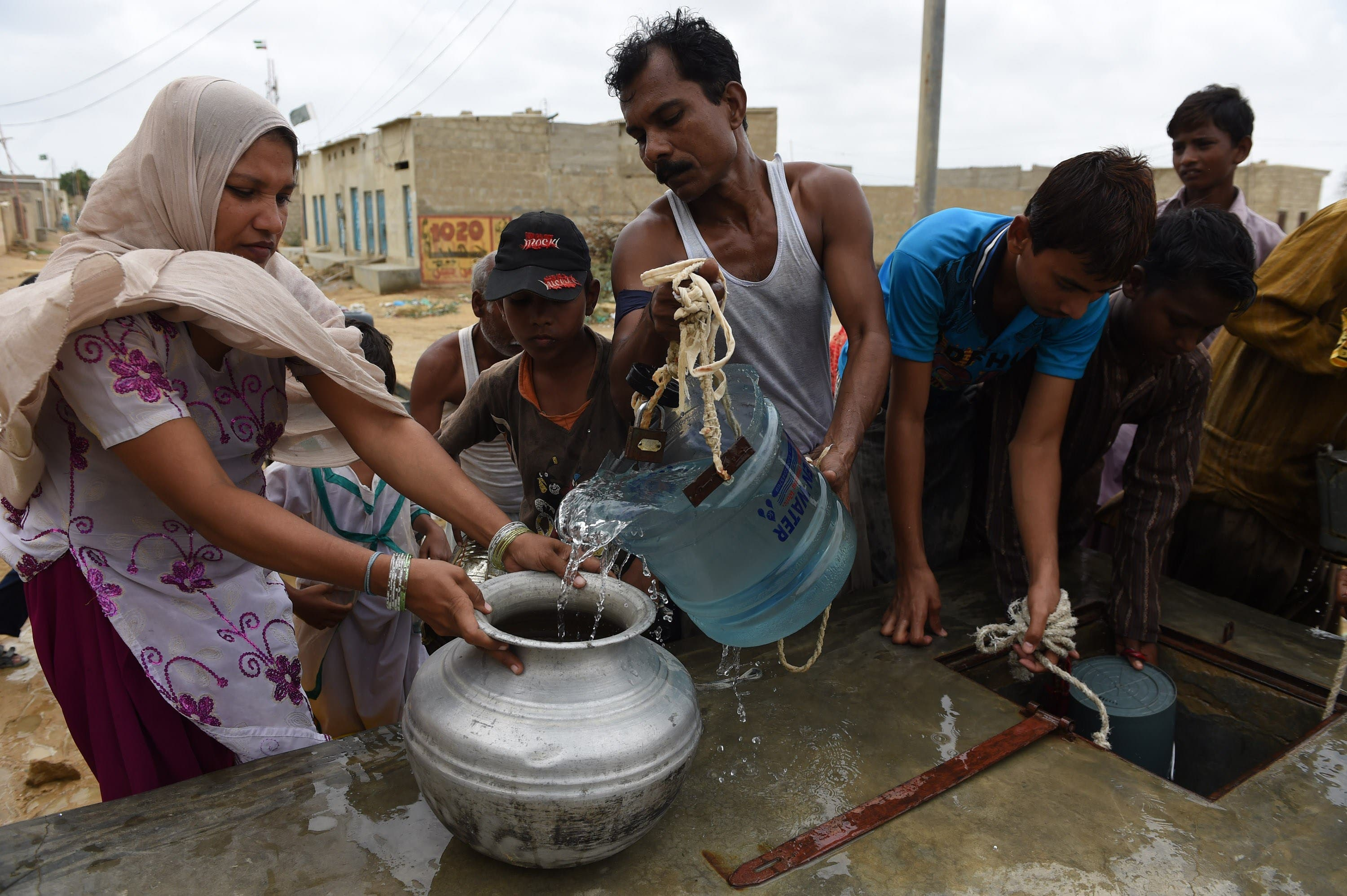 In this photograph taken on August 22, 2015, Pakistani residents fill containers with water provided by the government in a slum area of Karachi.