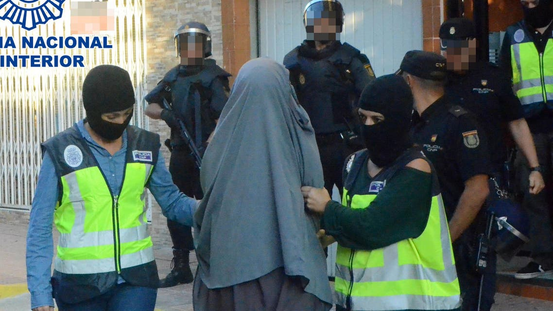 "This handout image released on October 4, 2015 by the Spanish Interior Ministry shows a person suspected of belonging to a ""network of recruitment, indoctrination,"" for ""sending foreign fighters to fight for Daesh (Islamic State) in the regions of Syria and Iraq"", being led away after arrest by Spanish authorities at an unspecified location on October 4, 2015. Police have arrested 10 people in Spain and Morocco for allegedly recruiting and indoctrinating fighters for the Islamic State group, the Spanish interior ministry announced today."