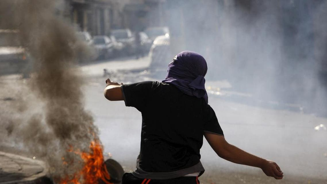 A Palestinian throws stones at Israeli army soldiers during clashes in the occupied West Bank city of Hebron Oct.  4, 2015. (Reuters)