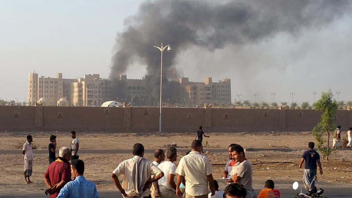 People watch as smoke billows from al-Qasr hotel after it was hit by explosions in the western suburbs of Yemen's southern port city of Aden. (Reuters)