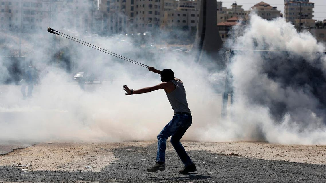 A Palestinian demonstrator uses a slingshot during clashes following a demonstration in the West Bank city of Ramallah. (AP)
