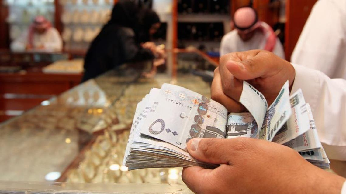 A salesman counts money at a jewellery shop at the gold market in Riyadh. (File photo: Reuters)