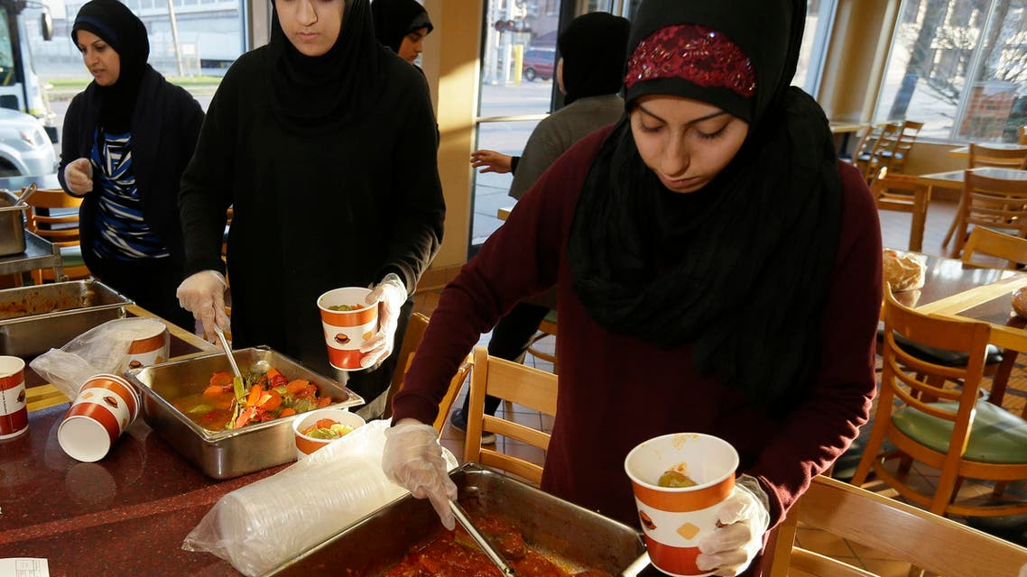 Volunteers Zahraa Debaja, center, and Zeinab Makki, right, prepare meals from food provided by the Yasmeen Bakery in Dearborn, Mich., Friday, April 25, 2014. (AP)