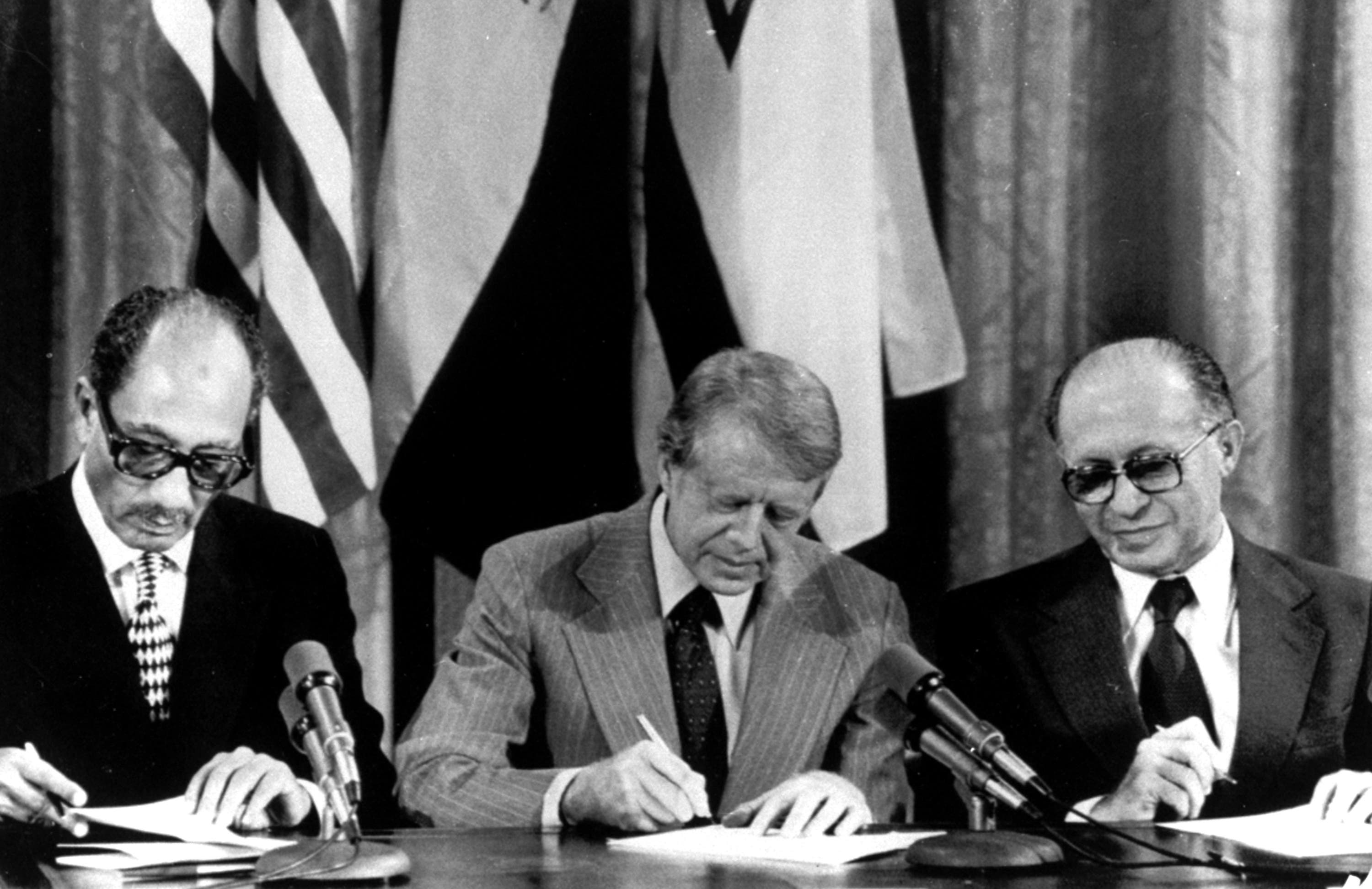From left, Egyptian President Anwar Sadat, U.S. President Jimmy Carter, and Israeli Prime Minister Menachem Begin sign one of two agreements forged at the Camp David Summit during a joint announcement at the White House, September 17, 1978.  (AP)