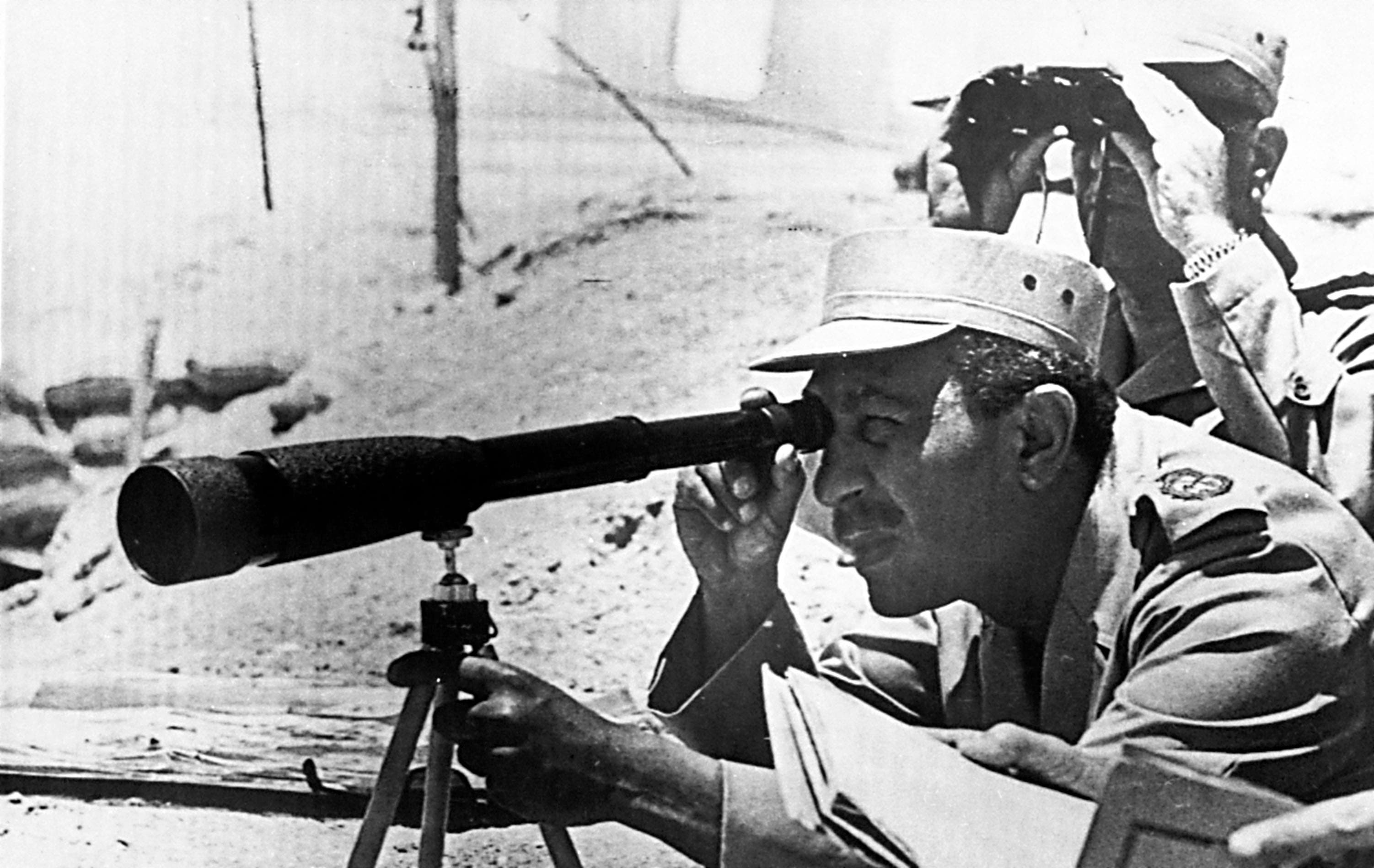 Making a plan: Egyptian President Anwar al-Sadat is seen as he peers through a telescope during a visit at the frontlines to Israel, at Sinai Peninsula, on June 4, 1973.