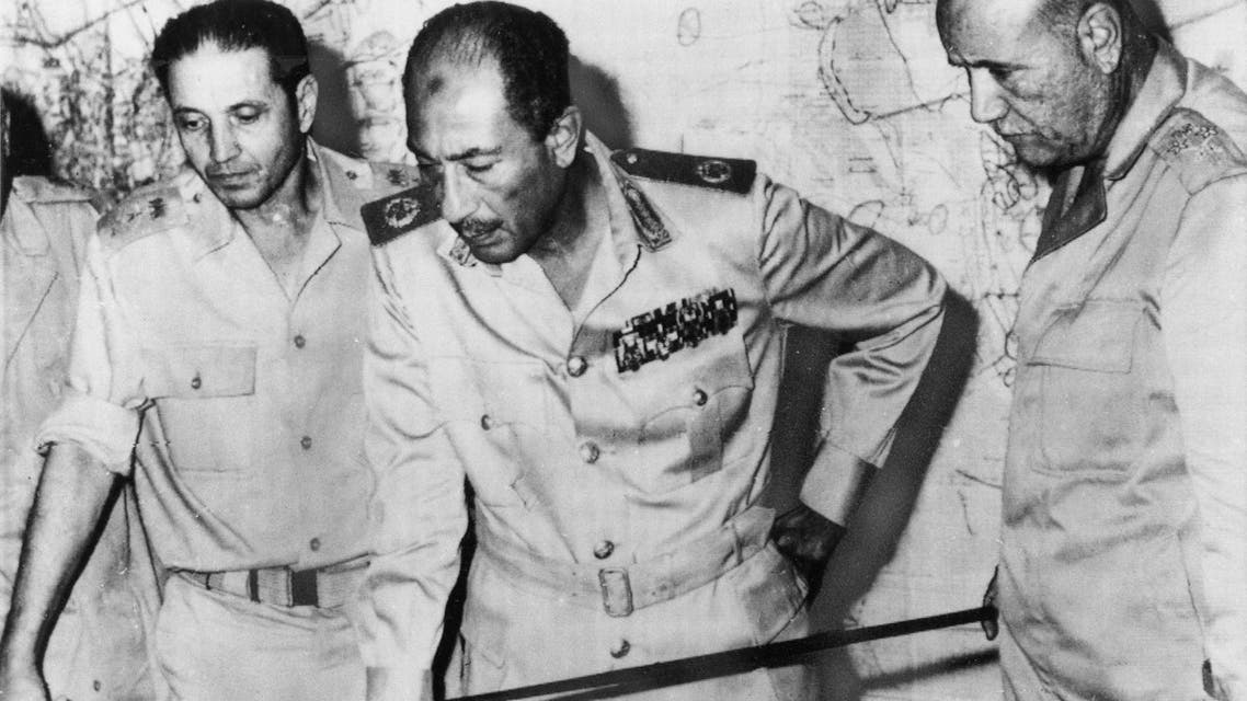 Egyptian President Anwar al-Sadat is flanked by officials as he reviews maps of battle development in the desert of Sinai Peninsula, at his Army headquarters in Cairo, on October 15, 1973 (AP)