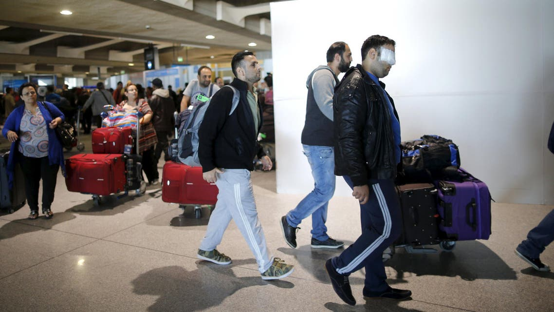 Christian Syrian refugee Walid Aleid (R), injured in a September bomb attack in Damascus, arrives with fifteen family members at the Charles-de-Gaulle Airport in Roissy from Beirut, October 2, 2015. A Syrian Christian family targeted by a September bomb attack in Damascus flew into Paris on Friday to start a new life, roughly a year after they requested entry visas from the French authorities. REUTERS/Stephane Mahe