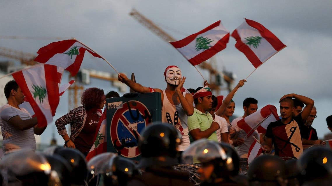 Protesters chant slogans as riot policemen block a street leading to the parliament building. (Reuters)