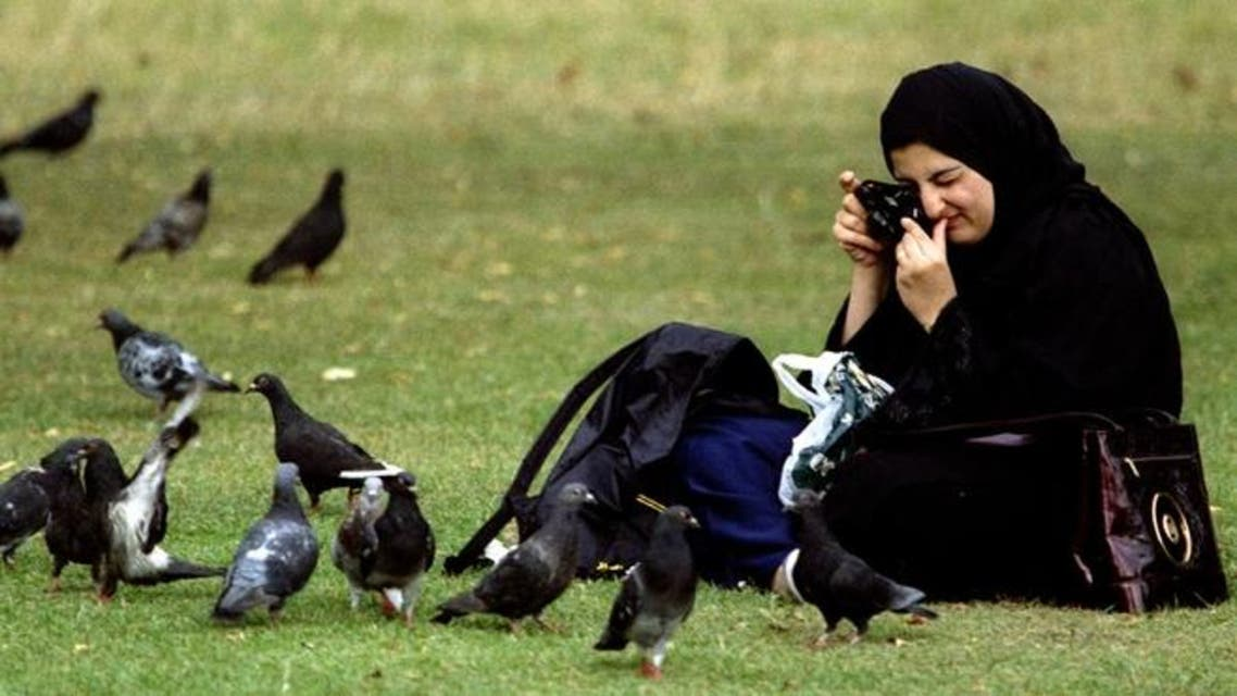 A woman from Saudi Arabia takes a picture of pigeons she was feeding in London's Kensington Gardens. (File photo: Reuters)