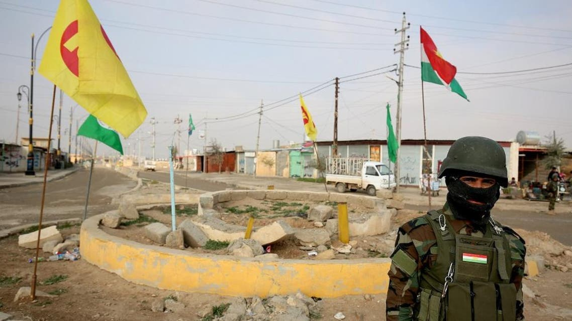 In this Jan. 29, 2015 file photo, a Kurdish peshmerga soldier of the Kurdish KDP party poses in front of KDP and PUK flags in the town of Snuny, close to Sinjar, northern Iraq. (AP)