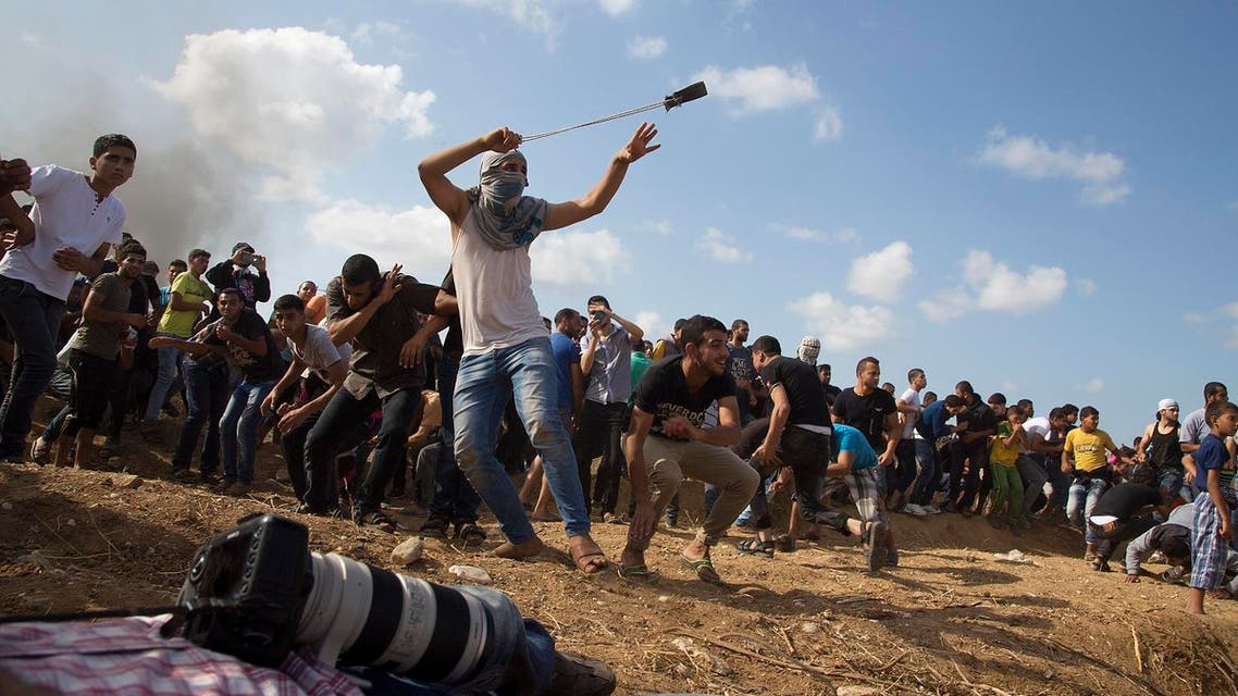 A Palestinian protester hurls stones at Israeli soldiers during clashes on the Israeli border Eastern Gaza. (AP)