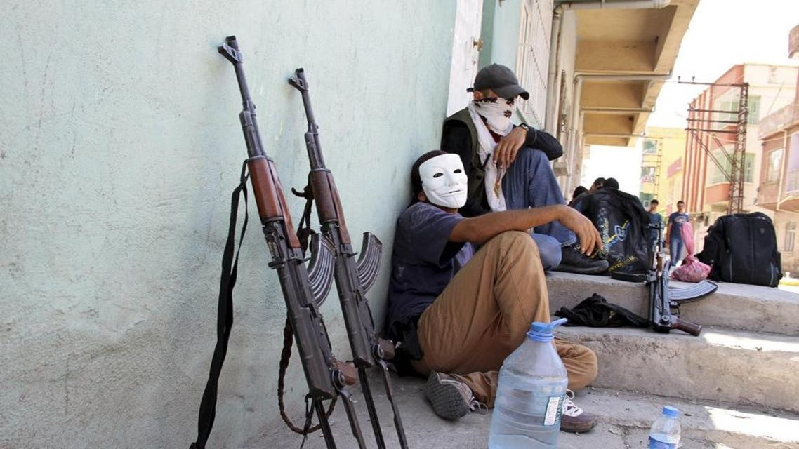 Masked members of YDG-H, youth wing of the outlawed Kurdistan Workers Party (PKK), sit next to their weapons in Silvan, near the southeastern city of Diyarbakir, Turkey. (File: Reuters)