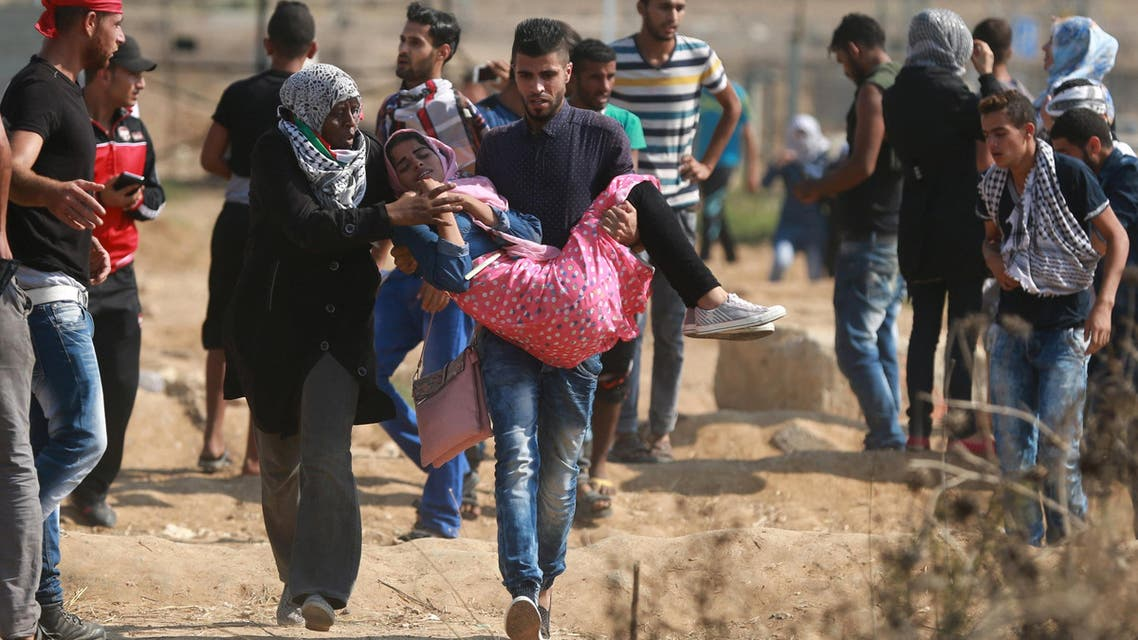 A Palestinian protester is evacuated after inhaling tear gas fired by Israeli troops during clashes near the Israeli border fence in the east of Gaza City October 10, 2015. (Reuters)