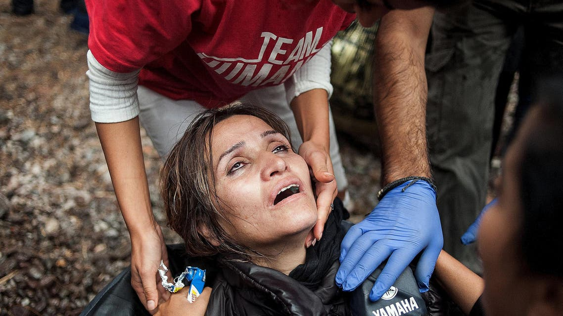 A migrant woman is helped by volunteers after arriving by an overcrowded dinghy on the Greek island of Lesbos, after crossing a part of the Aegean Sea from the Turkish coast to Lesbos October 10, 2015. REUTERS/Fotis Plegas