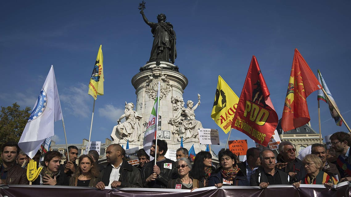 """9609 - Paris, Paris, FRANCE : People take part in a demonstration organised by the Kurdish Democratic Council of France on Place de la Republique in Paris, on October 11, 2015, in support of the victims of the suicide bomb attack which occured in Ankara on October 10. Turkey woke in mourning after at least 95 people were killed by suspected suicide bombers at a peace rally of leftist and pro-Kurdish activists in Ankara, the deadliest such attack in the country's recent history. Thousands also took to the streets in solidarity in Paris, Strasbourg and Marseille in France, as well as in Zurich in Switzerland. The banner reads """"Custody, Bloody Attacks, Isolation"""". AFP PHOTO / JOEL SAGET"""