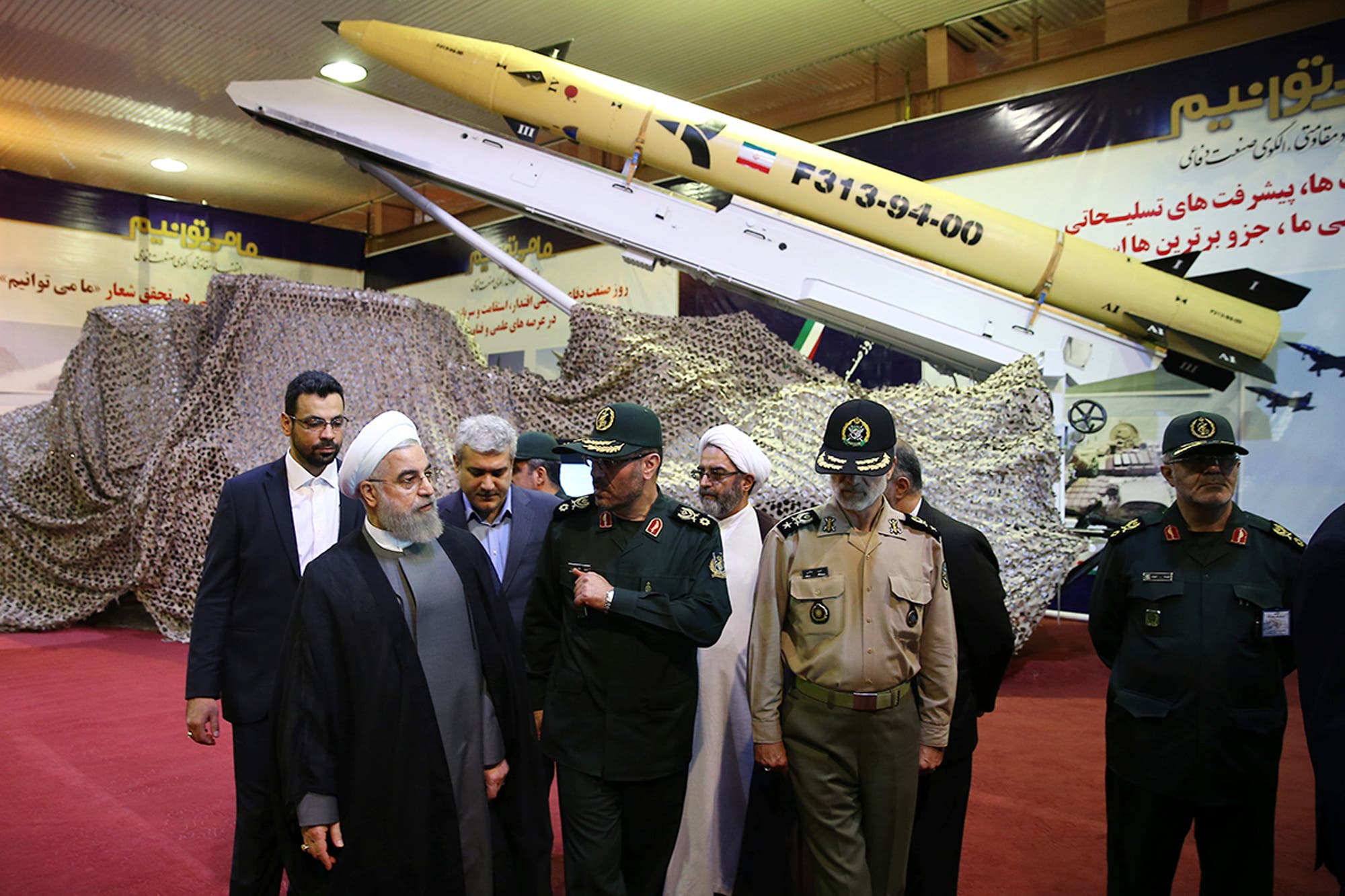 Iran's President Hassan Rouhani, left, listens to Defense Minister Hossein Dehghan after unveiling the surface-to-surface Fateh-313, or Conqueror, missile in a ceremony marking Defense Industry Day, Iran.