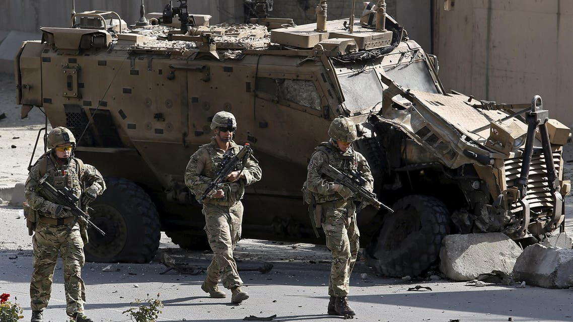 NATO soldiers walk in front of a damaged NATO military vehicle at the site of a suicide car bomb blast in Kabul, Afghanistan, October 11, 2015.
