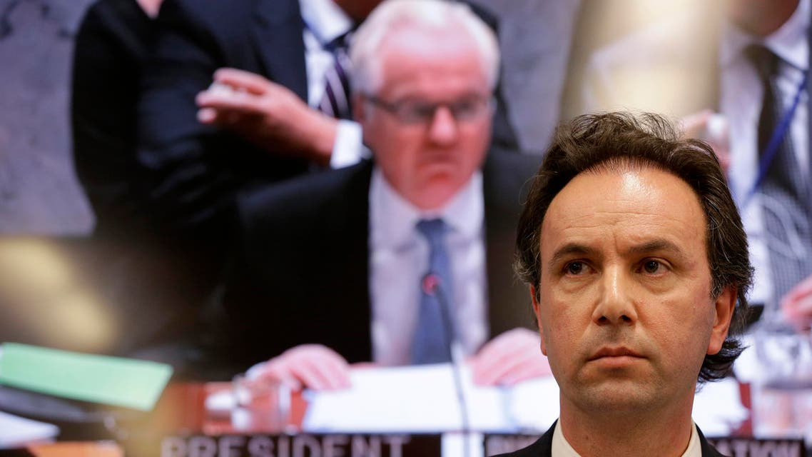 Khaled Khoja, president of the Syrian National Coalition, speaks to reporters during a news conference at United Nations headquarters on Wednesday, Sept. 30, 2015 as a video monitor in the background displays Russian Ambassador to the U.N. Vitaly Churkin presiding over a Security Council meeting. (AP Photo/Mary Altaffer)